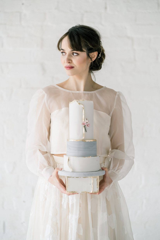 bride holding modern marbled cake with gold foiling details