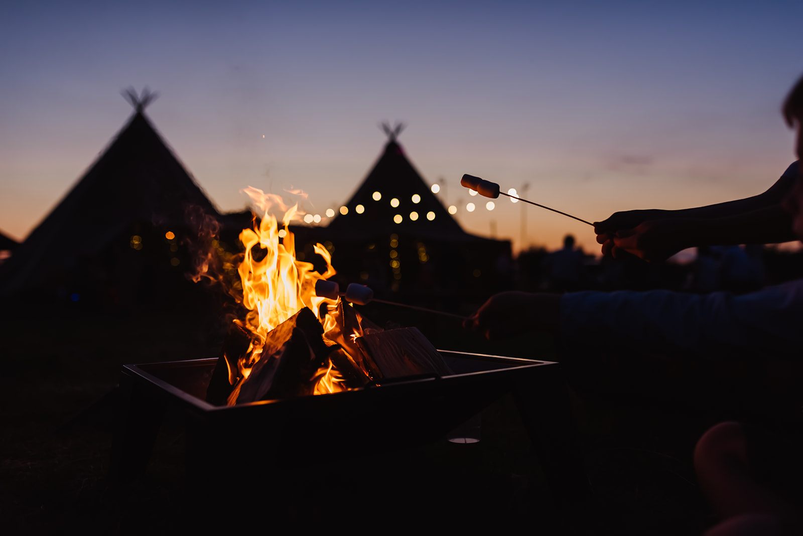 fire pit at tipi wedding toasting marshmallows at sunset