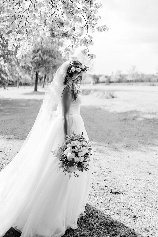 boho bride in flower crown holding flowers at wedding aynhoe