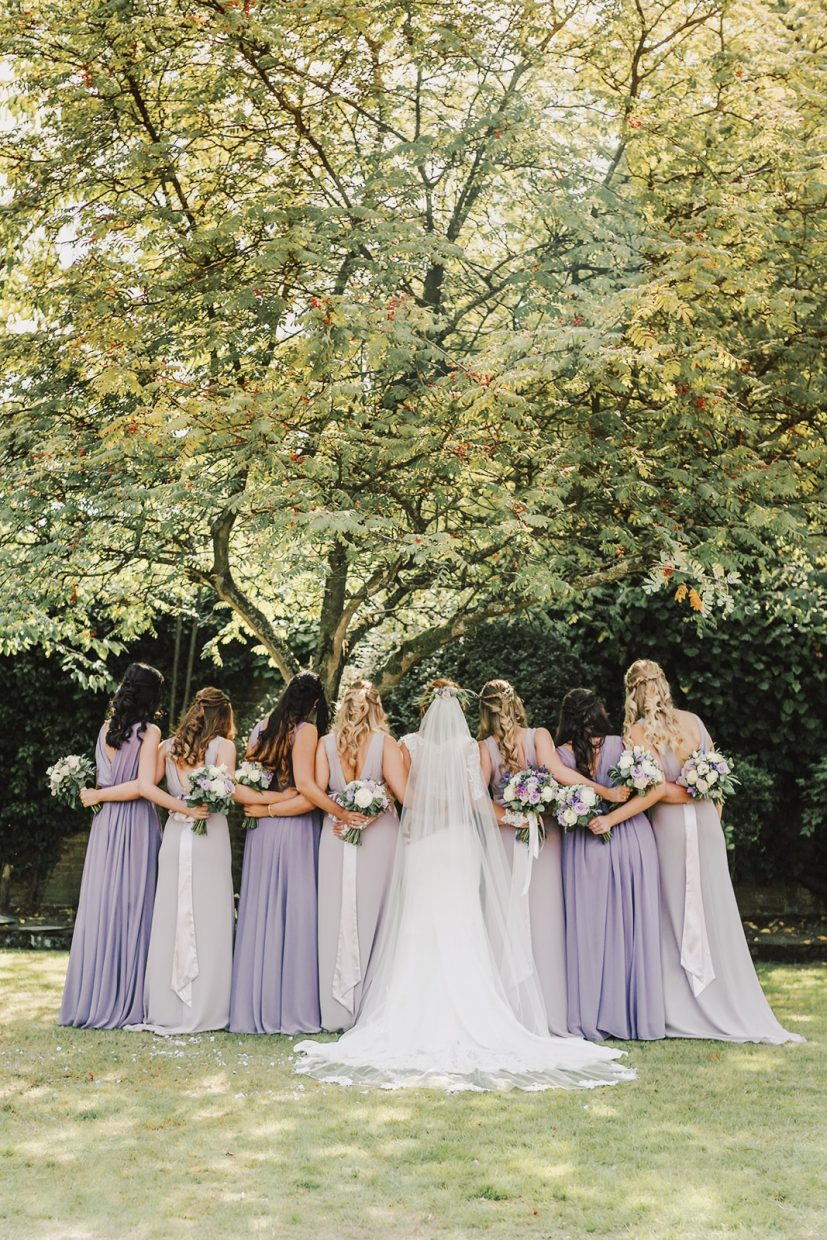 Bridesmaids backs with long hair and bouquets