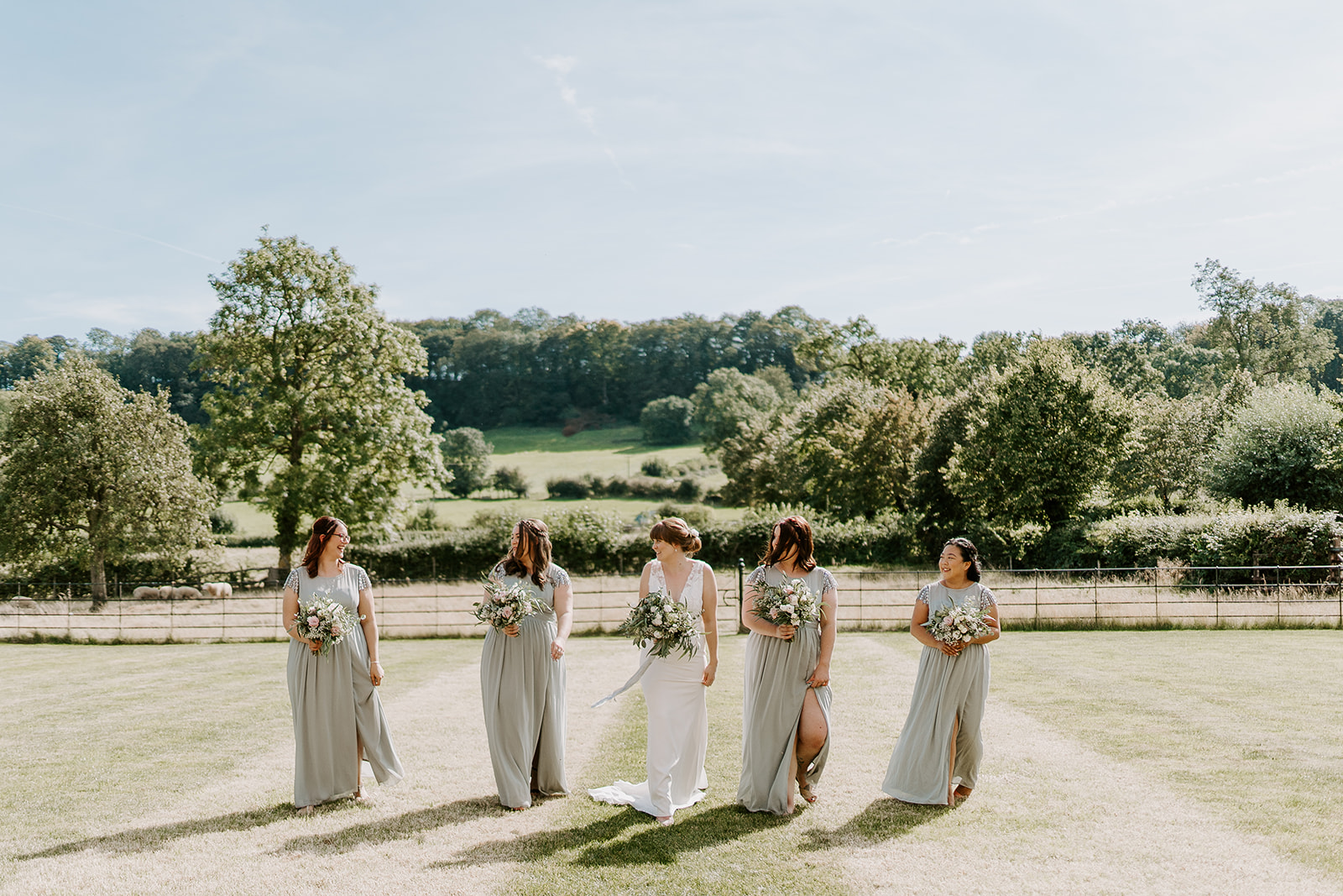 bride and bridesmaids laughing in sage green dresses with flowers