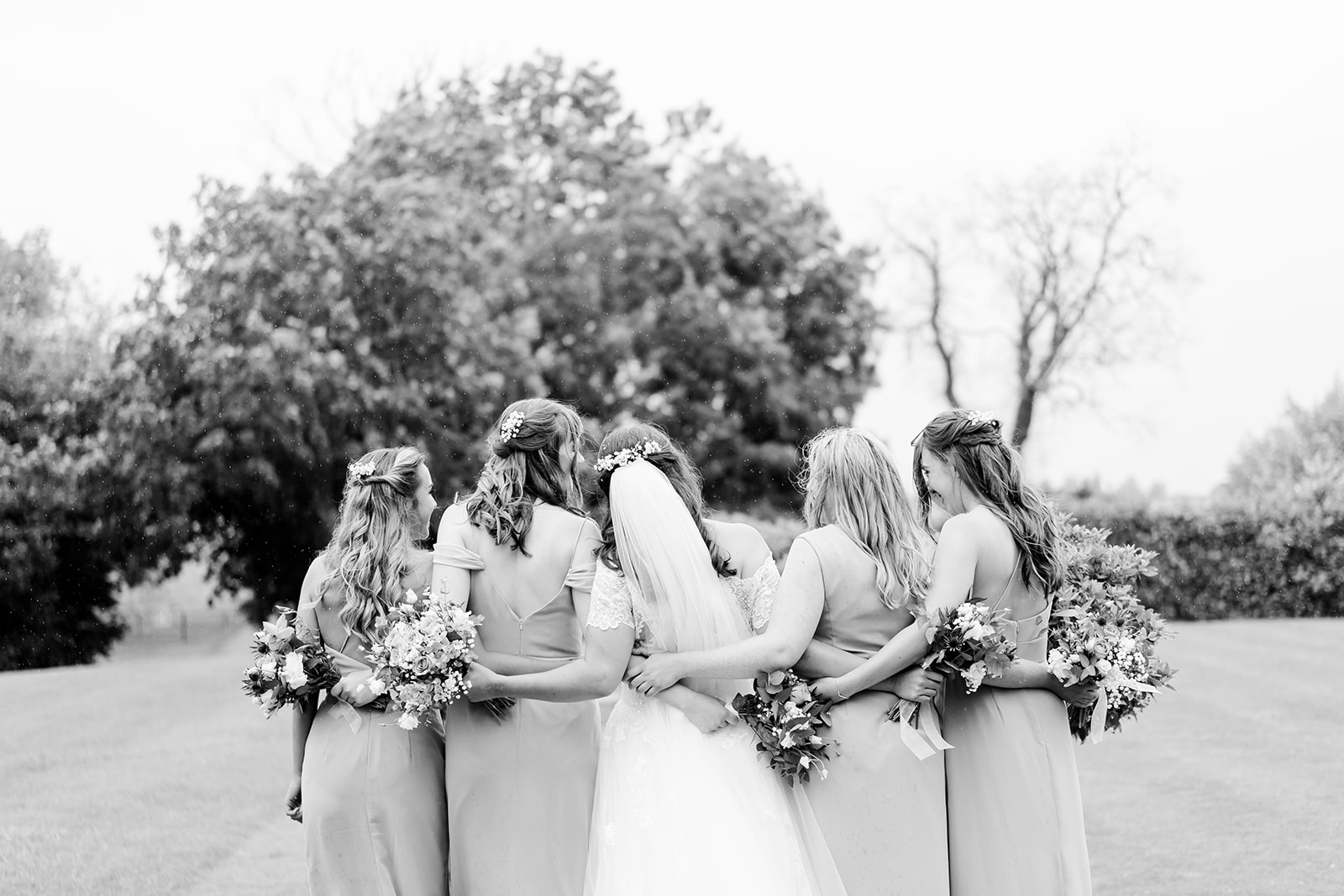 bride and bridesmaids hugging with flowers at Blackwell grange