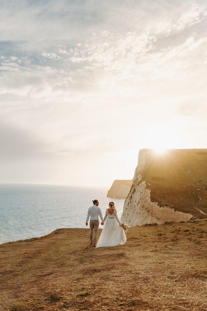boho Durdle Door elopement wedding at golden hour on beach cliffs