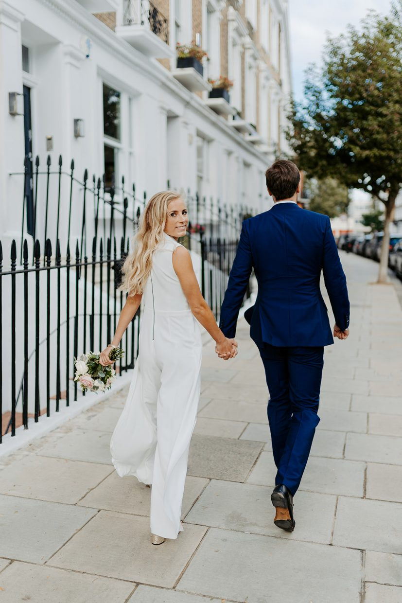 Bride in jumpsuit and Groom at Chelsea Town Hall wedding London
