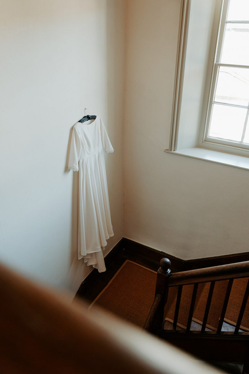dress hanging on staircase wedding photos wales